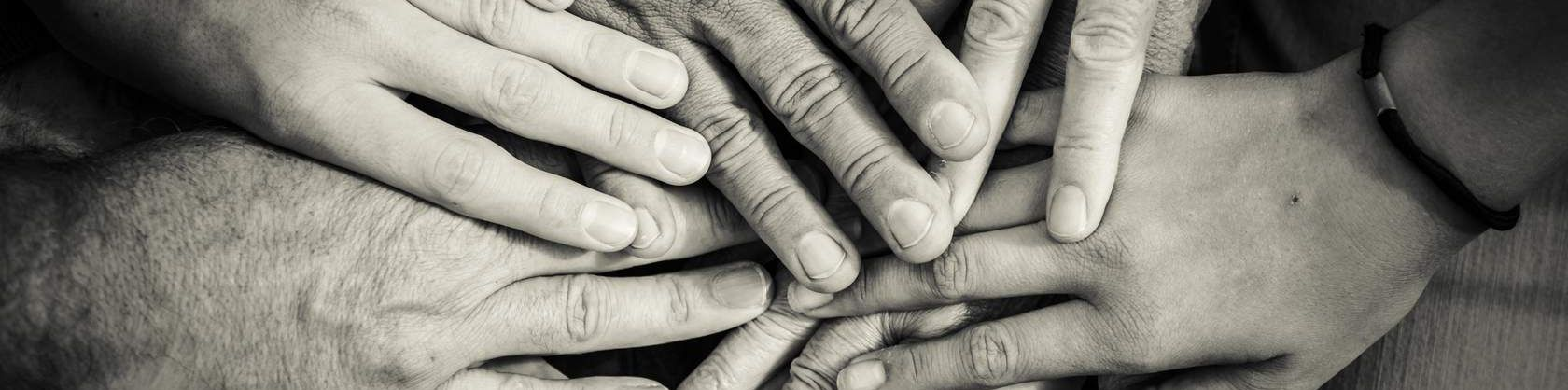 Black and white image of people's hands holding each other